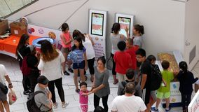 Top shot of people line up for signing up free contest on touch screen machine