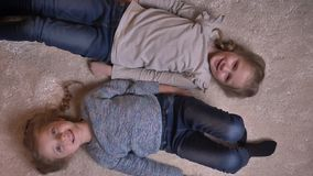 Top shot portrait of two small girls lying feet to head on the floor with opposite emotions. stock footage