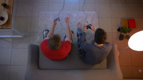 Top shot of two friends in sleepwear playing videogame together and ripping of the wire of joystick in the living room. Top shot of two friends in sleepwear stock video