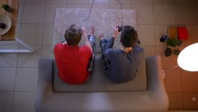 Top shot of two friends in sleepwear playing videogame together using joystick and giving five in the living room. Top shot of two friends in sleepwear playing stock footage