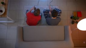 Top shot of two young guys in sleepwear playing videogame on the floor and emotionally reacting in the living room.