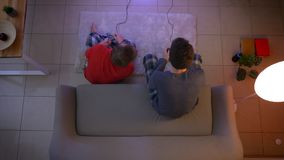 Top shot of two young guys in sleepwear playing videogame with joysticks sitting at sofa and on the floor.