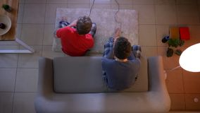 Top shot of two young guys in sleepwear playing videogame using joystick sitting at sofa and on the floor.
