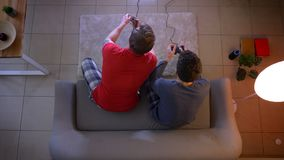 Top shot of two young guys in sleepwear playing videogame using joystick sitting at sofa in the living room.