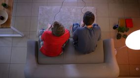 Top shot of two young guys in sleepwear playing videogame using joystick and talking with each other in the living room.