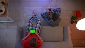 Top shot of two young guys in sleepwear playing videogame using joystick and working with tablet in the living room.