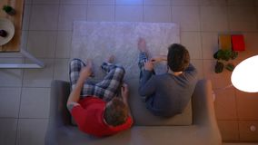 Top shot of two young guys in sleepwear sitting on sofa and communicating watching TV in the living room.