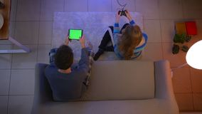 Top shot of young couple in sleepwear playing videogame with joystick and tablet in the living room. stock video footage