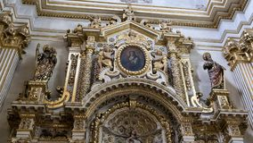 Top of a side Altar of the Duomo Cathedral featuring a statue of our Lady of the Assumption in Lecce, Italy. Pictured is a closeup view of the top of the side Royalty Free Stock Photos