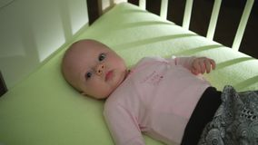 Top Side View of Adorable Baby in pink cloth lying on bed and moving hands and legs royalty free stock photography