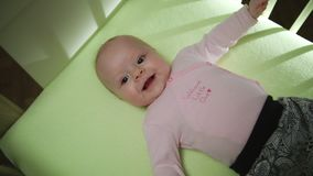 Top Side View of Adorable Smiling Baby in pink cloth lying on bed and moving hands and legs royalty free stock photos