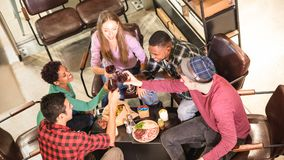 Top side view of multi racial friends tasting red wine at winery bar. Multi racial friends tasting red wine and having fun at cool fashion bar winery location stock photo