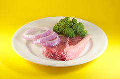 Top Sirloin. Nice raw red top sirloin steak served with broccoli and red onions on a white plate over yellow backgorund representing healthy eating Royalty Free Stock Photo