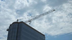Top of skyscraper and construction crane against the background of moving clouds stock video