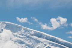 Top of a snow mountain with blue sky Stock Photos