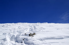 Top of snowy mountains with footpath and blue sky. In winter royalty free stock photography