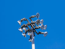 Top of stadium flood light tower on blue sky. Top of industrial stadium flood lights with twelve lamps on clear blue sky Stock Photography