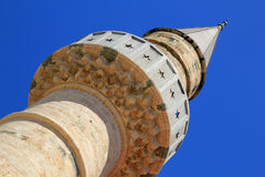 Top of stone minaret of ancient mosque on Greek Island of Kos. Top section of intricately carved ancient stone carved minaret tower of mosque on Kos Island in royalty free stock photos