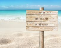 Top ten beaches in the world message on the sign board on the tropical white sandy beach background. Top ten beaches in the world message on the wooden planks stock photo