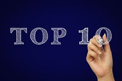 Top ten text concept written in doodle style by hand with dark blue background