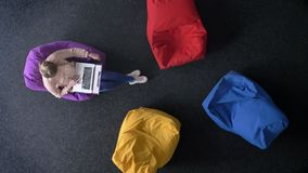 Top-tiro de la mujer joven que trabaja con el ordenador portátil en los bolsos multicolores suaves que cambian asientos secuencia metrajes