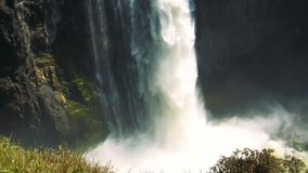 Top to bottom pan of water falling at Victoria Falls. Wide top to bottom tilt shot of water falling at Victoria Falls in slow motion at sunset stock video footage