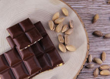 Top to Ripe Nuts and Biiter Chocolate Wood Background. Ripe Nuts and Chocolate Concept and Decoration royalty free stock images