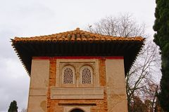 Top of a tower, detail of Alhambra medieval moorish castle, Granada. Top of a tower, with roof tiles and windows with decorative stone carvings detail of Nassrid Stock Images