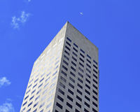 The top of a towering skyscraper in front of blue sky. In a city, with an airplane flying high overhead Stock Photography