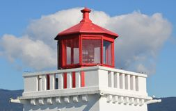 Historic Beacon Light. The top of a traditional red and white beacon used for maritime safety with cumulus clouds in the background Royalty Free Stock Images
