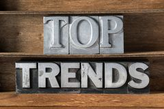 Top trends tray. Top trends phrase made from metallic letterpress type on wooden tray royalty free stock photography