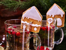 Top two glass latte mug hot drink under fir branch . Top of two glass latte mug hot drink. Warming mulled wine with cookie in form of house under fir branch in royalty free stock photos