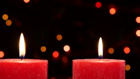 Top of two red candles with christmas decorations. Top of two big red candles with christmas decorations on black background, bokeh, light, garland stock video footage