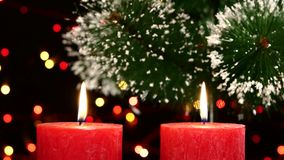 Top of two red candles with christmas decorations. Top of two big red candles with christmas decorations and tree on black background, bokeh, light, garland stock video