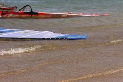 The top of two sail board sails floating in shallow water. Near sand on the beach stock photo