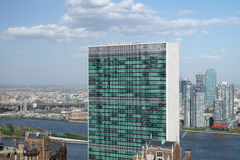 Top of United nations secretariat building with puffy white clou. Ds above it - May 2, 2017, 1st Avenue, New York City, NY, USA Stock Image