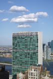 Top of United nations secretariat building with puffy white clou Stock Photos