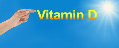 Top up your Vitamin D with sunshine. Wide sunshine and blue sky background with the word Vitamin D and a female hand pointing at the Vitamin D word plus copy stock images