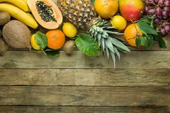 Top Upper Border with Copy Space from Fresh Tropical Fruits Pineapple Papaya Mango Coconut Oranges Kiwi Bananas Lemons Grapefruit. On Wood Background. Healthy Royalty Free Stock Photo