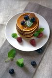 Homemade pancakes with forest fruits berries on white table. Fresh pancakes on plate tablecloth. Blueberries, raspberries, mint on royalty free stock image