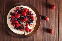 Top viev. Delicious Homemade creamy mascarpone New York Cheesecake with berries on dark wooden table. Close up. royalty free stock photo