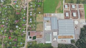 Top view above several houses surrounded by green lawns and agricultural area. Top view above houses surrounded by green lawns, rural long roads, concrete stock footage