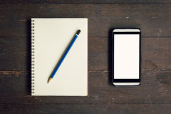 Top view above notebook and pencil with phone Royalty Free Stock Photo