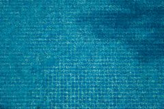 Top view of abstract blurred texture of blue wave water with mosaic tiles in swimming pool. Top view of abstract blurred texture of blue wave water with mosaic Stock Photography
