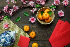 Top view accessories Chinese new year festival decorations.orange,leaf,wood basket,red packet,plum blossom,teapot on wooden table. Background