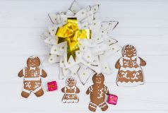 Top view of adorable homemade gingerbread Christmas tree with cute gingerbread family with gifts on white wooden desk. Mockup for seasonal offers and holiday Royalty Free Stock Images