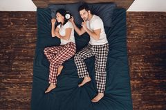 Top view. Adult handsome man plans to wake up with alarm clock sleeping young woman lying on bed. stock image