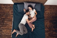 Top view. Adult happy man in pajamas lies and hugs pregnant smiling woman on bed. stock photography