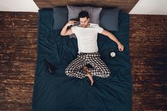 Top view. Adult man lies in bed next to alarm clock and bottle of wine, attaching gun to temple. stock image