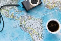 Top view of adventure flat lay with coffee cup and camera. Explore the new world or planing the vacation. With cup of coffee royalty free stock photo